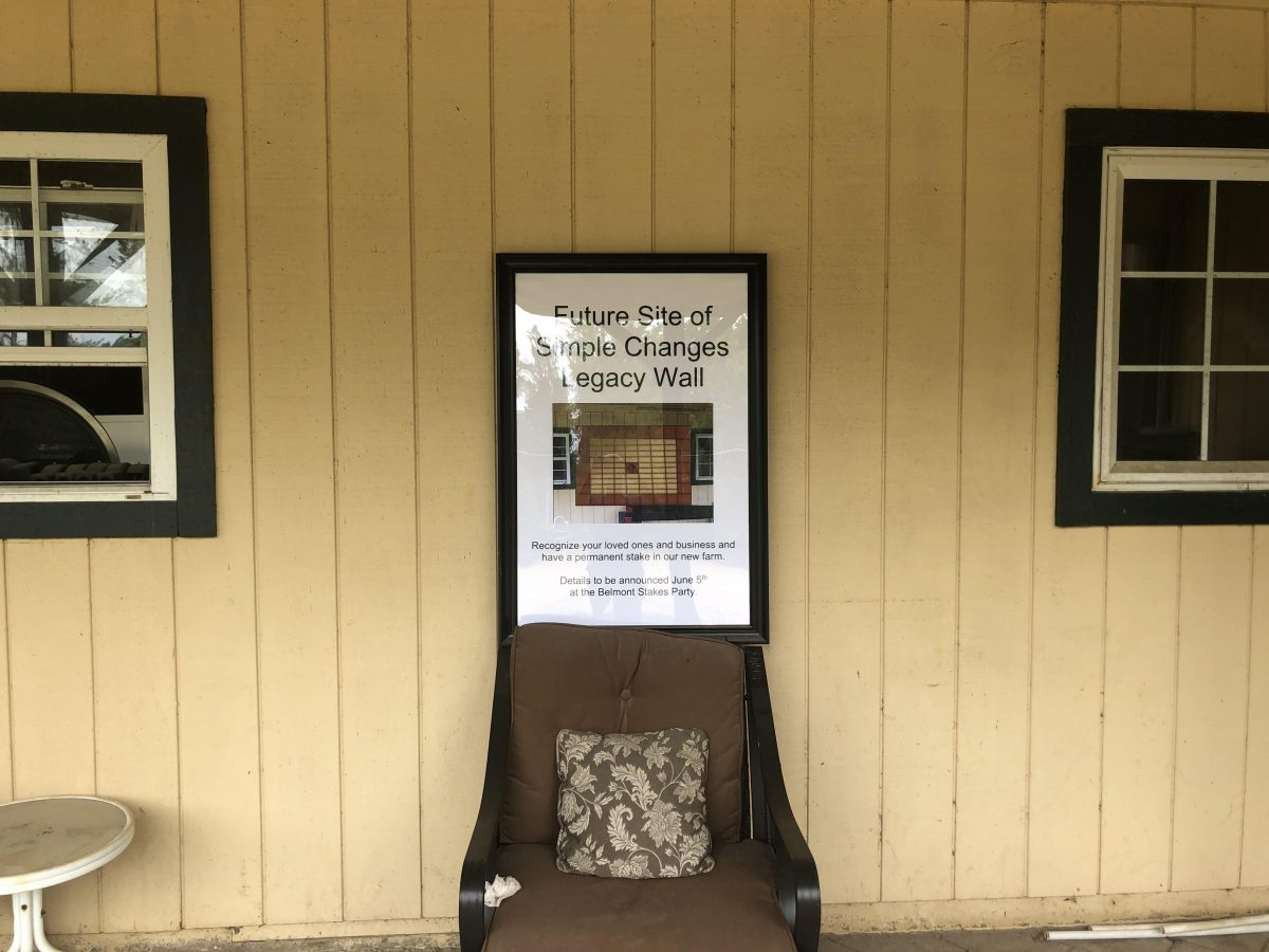 """The side of the barn displaying a framed poster that says """"Future Site of Simple Changes Legacy Wall."""""""