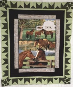A quilt depicts a scene of 7 horses in a pasture. There is a tree and a white barn in the background and 2 of the horses are standing in a pond in the middle. The border of the quilt is a geometric pattern in light and dark green.